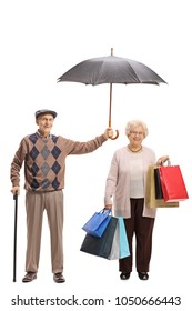 Full length portrait of an elderly gentleman holding an umbrella over an elderly woman with shopping bags isolated on white background
