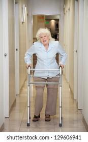 Full length portrait of an elderly woman with walker standing in hospital corridor