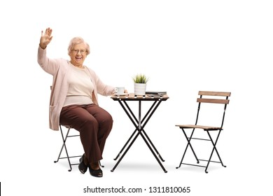 Full length portrait of an elderly woman sitting at a table with a cup of coffee and waving isolated on white background