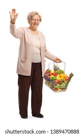 Full length portrait of an elderly woman with fruits and vegetables in a shopping basket waving with her hand isolated on white background