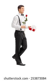 Full length portrait of an elegant guy walking with a rose and a present isolated on white background