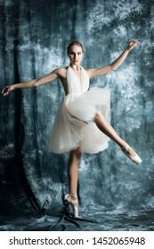 A full length portrait of an elegant refined female ballet dancer posing in the studio over the grunge background. Talent, fashion for ballet dancers.