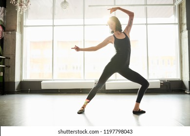 Full length portrait of elegant young woman dancing in studio lit by serene sunlight, copy space