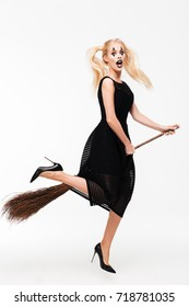 Full length portrait of a excited cheerful blonde woman dressed in witch halloween costume standing with a broom and looking at camera isolated over white background