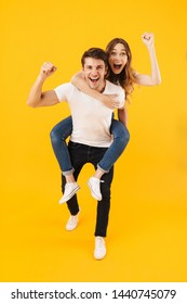 Full length portrait of excited couple man and woman in basic t-shirts having fun together while doing piggyback ride isolated over yellow background