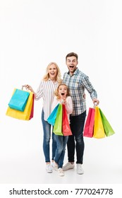 Full length portrait of an excited family holding paper shopping bags isolated over white background