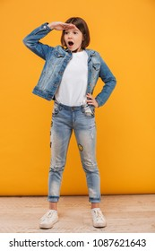 Full length portrait of an excited little schoolgirl standing and looking far away over yellow background