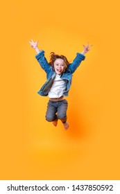 Full length portrait of an excited little curly girl jumping over orange background