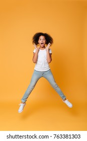 Full length portrait of an excited little african girl jumping and celebrating isolated over orange background