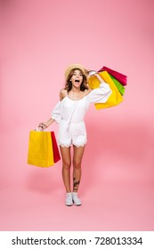 Full length portrait of an excited satisfied girl holding shopping bags while standing and looking looking far away with a hand at her forehead isolated over pink background