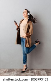 Full length portrait of an excited young asian woman listening to music with headphones while holding mobile phone and dancing over gray background