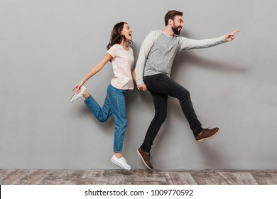 Full length portrait of an excited young couple jumping together and pointing away over gray background
