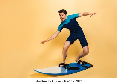Full length portrait of an excited young man dressed in swimsuit surfing on a board isolated over yellow background