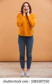Full length portrait of an excited young woman in sweater with mouth open over yellow background