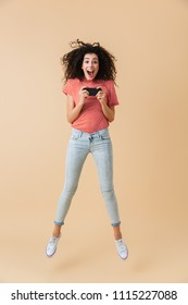 Full length portrait of an excited young girl playing games on mobile phone while jumping isolated over beige background
