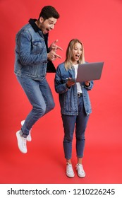 Full length portrait of an excited young couple dressed in denim jackets jumping together isolated over red background, looking at laptop computer