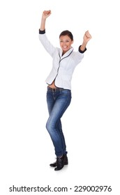 Full length portrait of excited young woman in smart casuals celebrating success against white background