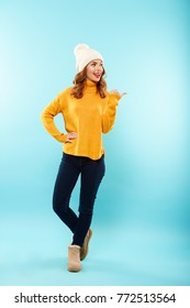 Full length portrait of an excited young girl dressed in winter clothes standing and pointing finger away isolated over blue background