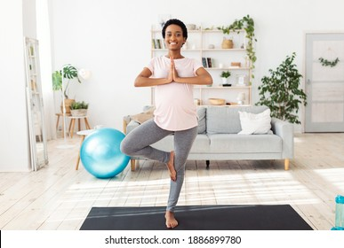Full length portrait of expectant young lady doing her morning yoga practice, standing in tree pose, feeling peaceful at home. Pregnant black woman having domestic workout during coronavirus pandemic