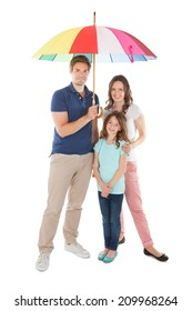 Full length portrait of family standing together below umbrella against white background