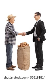 Full length portrait of a farmer with a burlap sack filled with potatoes shaking hand with a businessman isolated on white background