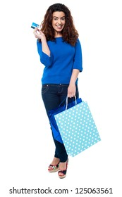 Full length portrait of a fashionable woman posing with shopping bags and credit card.
