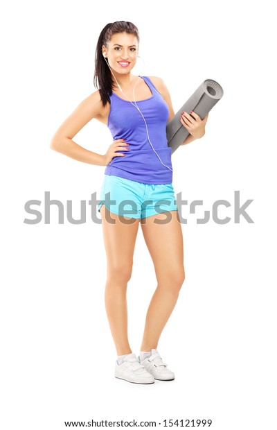Full length portrait of a female athlete  listening music and holding a mat, isolated against white background