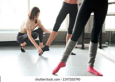 Full length portrait of female ballet teacher positioning feet of unrecognizable students in dance class, copy space