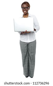 Full length portrait of female business secretary working on laptop