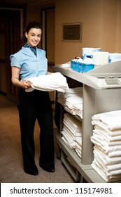 Full length portrait of female executive holding bath towel and standing beside the housekeeping cart