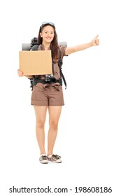 Full length portrait of a female hitchhiker holding a blank carton sign isolated on white background