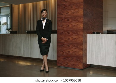 Full length portrait of female hotel receptionist standing at workplace. Beautiful woman receptionist working in hotel.