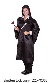 Full length portrait of a female judge in a gown carrying a law book and a wooden gavel as she prepares to go to court isolated on white