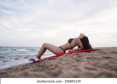 Full length portrait of female lies with surfboard against blue sea and calm sky background with copy space area for text message or advertise content, young sexy woman relax after swimming in summer