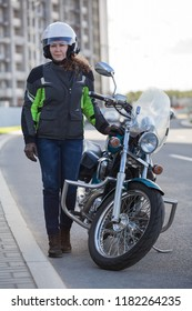 Full length portrait of female motorcyclist in safety outfit standing near classic bike on urban road
