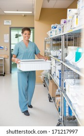 Full length portrait of female nurse carrying container in hospital storage room