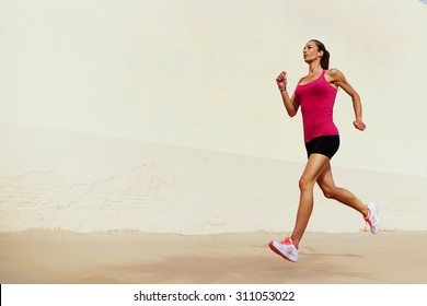 Full length portrait of female runner on morning jog against with copy space area wall for your text message or information, healthy sports woman with sexy figure playing sports outdoors in summer day