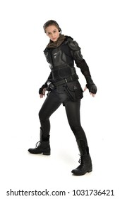 full length portrait of female  soldier wearing black  tactical armour and headset standing pose , isolated on white studio background.