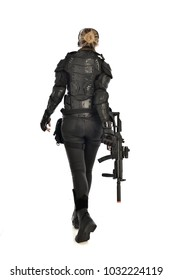 full length portrait of female  soldier wearing black  tactical armour  holding a gun, facing away from camera, isolated on white studio background.