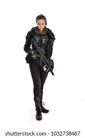 full length portrait of female  soldier wearing black  tactical armour  holding a gun, isolated on white studio background.
