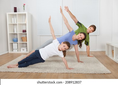 Full length portrait of fit family doing side plank yoga on rug at home