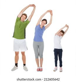 Full length portrait of fit family doing stretching exercise against white background