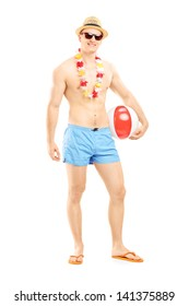 Full length portrait of a fit man in swimming shorts, holding a beach ball, isolated on white background