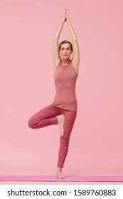 Full length portrait of fit mature woman doing yoga against pastel pink background, tree pose