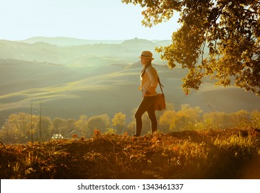 Full length portrait of fit solo traveller woman in hiking clothes with bag on summer Tuscany trekking looking into the distance.