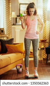 Full length portrait of fit woman in sport clothes in the modern living room standing at smart scale and tracking weight in a fitness app in a smartphone.