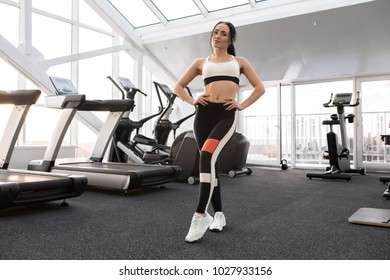 Full length portrait of fit young woman wearing sports clothes posing in modern gym smiling happily at camera, copy space