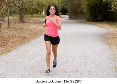 Full length portrait of a fit young woman jogging on a country road running towards the camera with her long hair flying out to the side, with copyspace