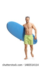 Full length portrait of a fit young man walking towards the camera and carrying a surfboard isolated on white background
