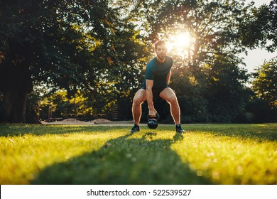 Full length portrait of fitness young man training with kettlebell in the park. Fit caucasian model doing physical workout in the park.